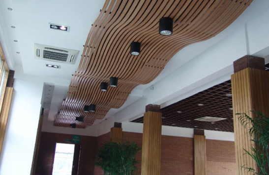 生态木吊顶效果图三 生态木吊顶效果图三中的生态木吊顶以流水为设计灵感来源,而且波浪一浪接着一浪。一直绵延下去,给人感觉水天相接,同时又不缺少绿色来点缀,营造了一种水生木的感觉。在波浪中,设计师又把灯融入其中,这些灯犹如一座座灯塔,指引着人们前进。总体来说,这块吊顶还是以简约大方为主借鉴了大自然的元素,可以说是自然和人文的很好的结合,是一款很不错的生态木吊顶设计。  生态木吊顶效果图四 生态木吊顶效果图四中的生态木吊顶主要体现在整体感上,不仅仅是吊顶为木结构,包括三个象征意义上的门,周围的墙的装修都属于木结